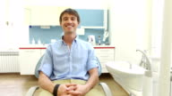 Man with beautiful white smile sitting in dental chair and looking at camera video