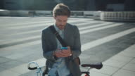 Man with bike using his smartphone video