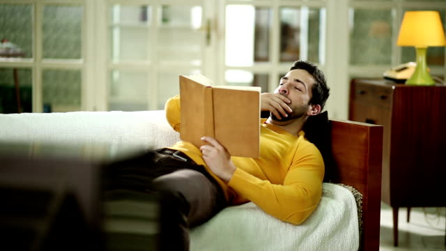 Man with book napping on the sofa video