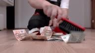 Man with brush sweeps euros in garbage scoop video