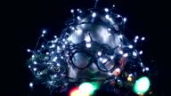 Man with christmas lights on head, turns, blinking, glasses, motion video