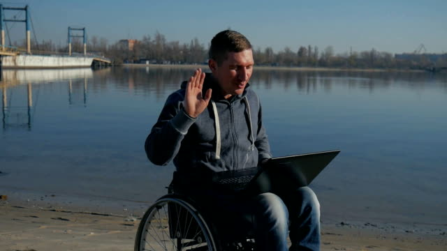 man with disability leads video chat on laptop, physically disabled man video