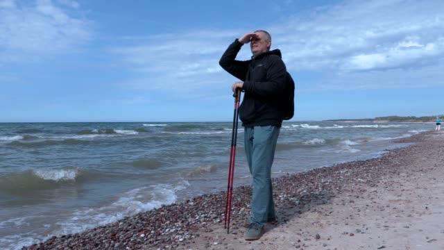 Man with hiking sticks at beach near sea video