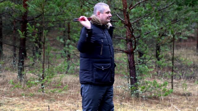 Man with hiking sticks warm up in forest video