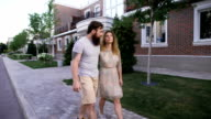 Man with his girlfriend walking down the sidewalk in the city video