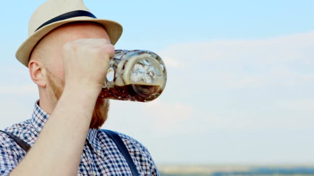 Man with leather suspenders outdoors drinking beer video