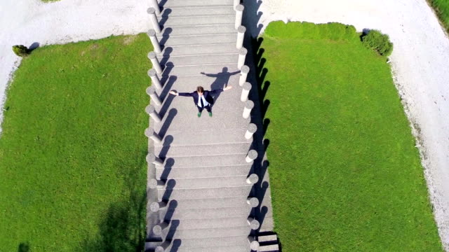 Man with raised hands stand on a stairs to heaven video