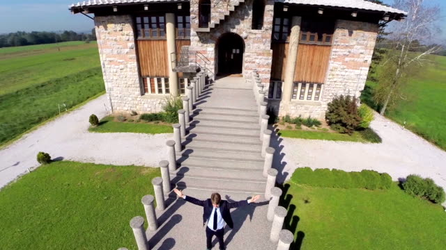 Man with raised hands stands in front of the church video