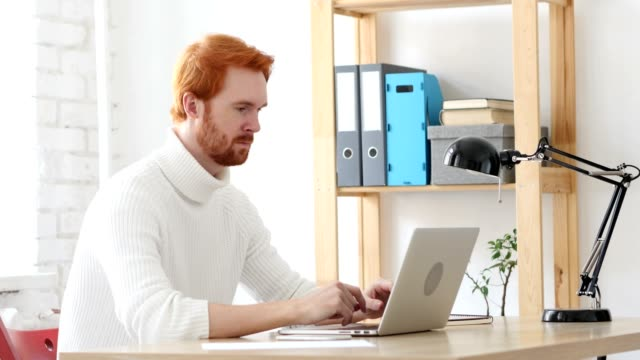 Man with Red Hairs Typing On Laptop in Office video