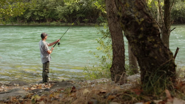 Man with rod fishing trout on river in Italy video