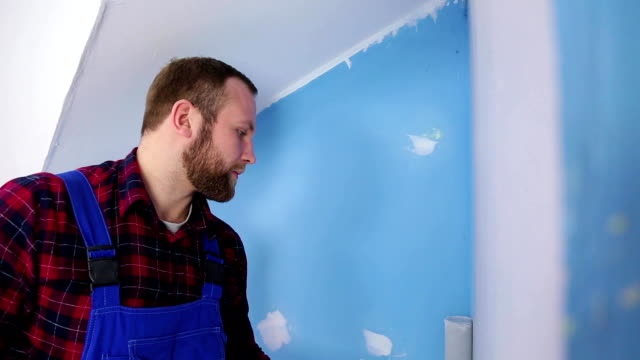 man with roller painting wall video