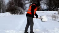 Man with snow shovel on the snovy road in winter video