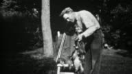 1934: Man with stringers of dead hunted birds smiles at dog. video