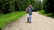 Man with suitcase on rural road video