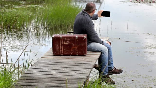 Man with suitcase sitting near lake and take pictures video