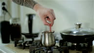 A man with tattoos stirring coffee using a spoon. video