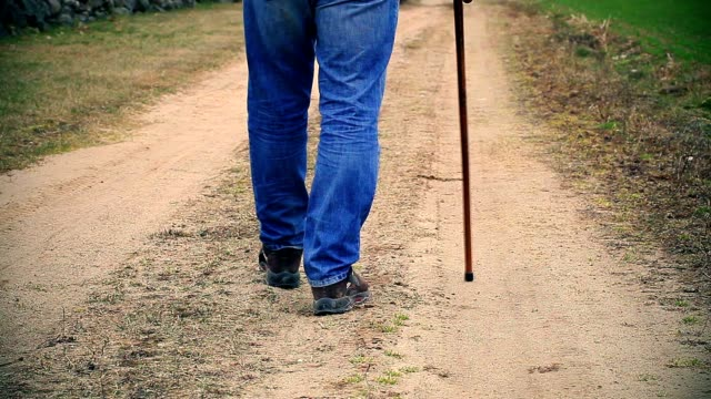 Man with walking stick walking away down the road video