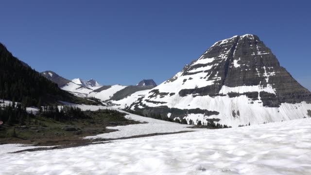 Man woman couple hike Glacier National Park Logan Pass snowfield Bearhat Mountain Montana video