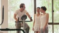 Man, woman, friends talking in hotel gym, fitness club, sports video