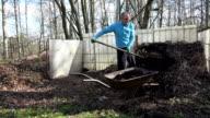 man work hard with fork in yard. Compost loading in wheelbarrow. video