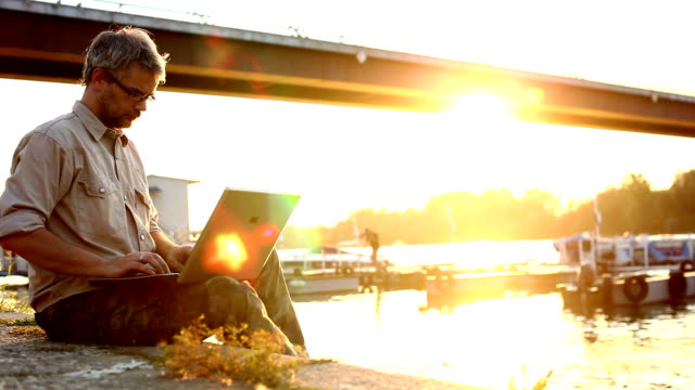 Man working on computer in sunset outdoor video