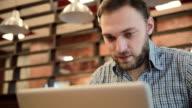 Man working on modern laptop in cafe video