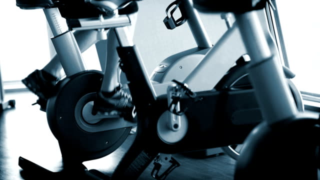 Man working out on the exercise bike at the hotel's gym blue sepia video