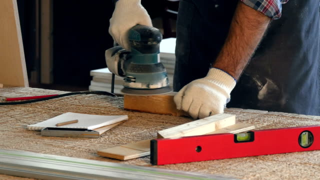 Man working with wooden planck and electric planer in workshop video