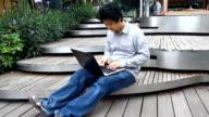 man works on his laptop to get all his business done early in the morning, outdoor video