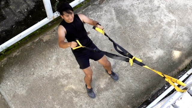 Man works out by using rope exercise training video