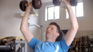 Man works out with dumbbells on a bench at a gym, front view video