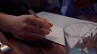 Man write marks on paper list by pen at table in restaurant. Glass. Fork video