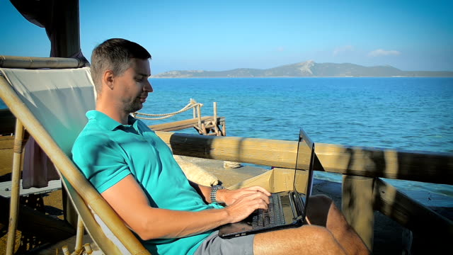Man Writing a Letter on the Laptop at a Resort Near the Sea video