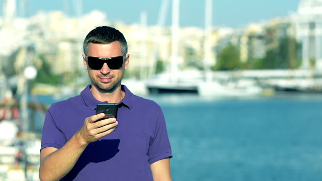 Man writing message on the smart-phone in the yacht club video