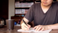 man writing on notebook and drinking coffee at home video