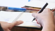 Man writing on notebook video