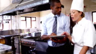 Manager and chef discussing on digital tablet video
