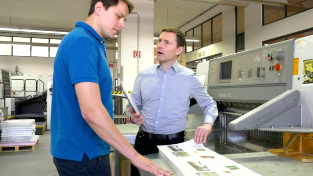 Manager discussing over printout with worker video