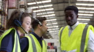 Manager giving instructions to warehouse staff, shot on R3D video