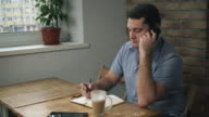 Manager in a blue shirt sitting in cafe, talking on phone, taking notes on a pad. On the table is a cup of latte next to the diary is a tablet video