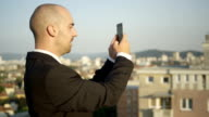 CLOSE UP: Manager taking panoramic picture standing on rooftop of a skyscraper video