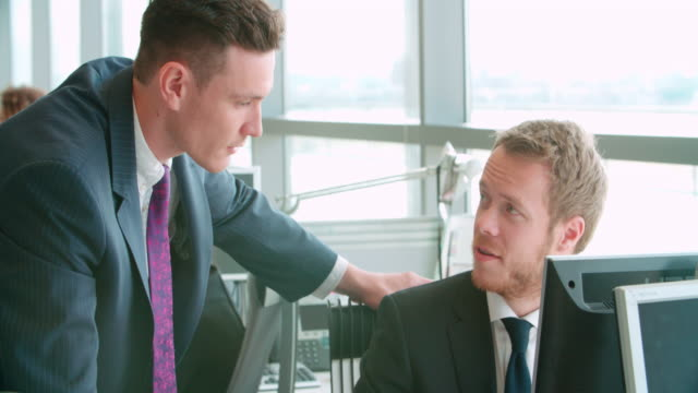 Manager talking with two colleagues in busy open plan office video