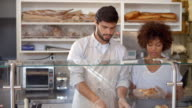 Manager training a woman behind the counter at sandwich bar video