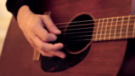 Man's hand touches on strings of acoustic guitar by mediator. Close up video