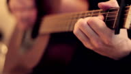 Man's hands playing acoustic guitar by mediator. Fretboard focus in out video