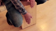 Man's hands to beat off a rhythm on wooden box isdide room video