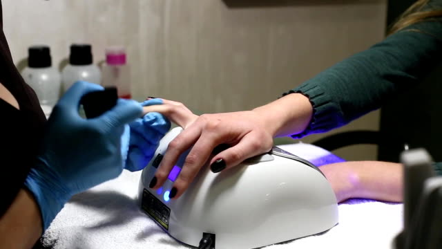 manicurist makes the manicure for young caucasian woman in beauty salon. hands close up video