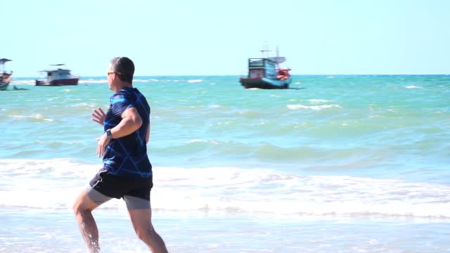 mann läuft mit laufschuhen und kurzer hose am strand von bang tao, phuket, thailand video