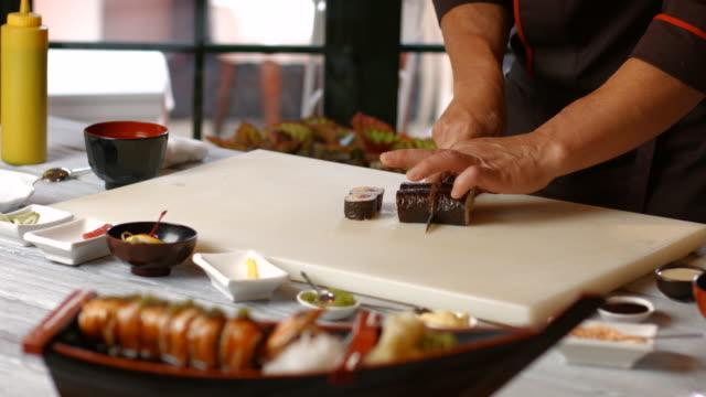 Man's hand cutting sushi rolls. video
