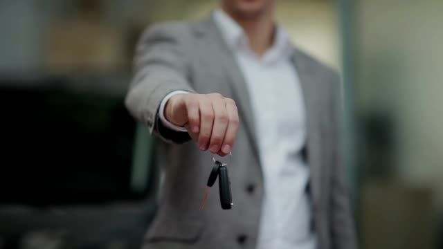 Man's hand handing a car key video